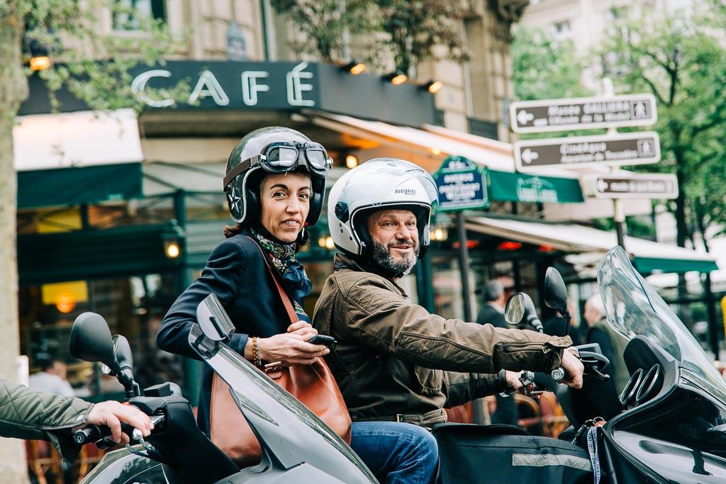 Ett leende par på vespa i Paris